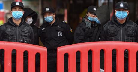 Police officers and security guards stand outside the Huanan Seafood Wholesale Market where the coronavirus was detected in Wuhan on Jan. 24, 2020.